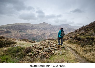 Female hiker with waterproof coat and backpack enjoying the view from the top of a hill in the Snowdonia National Park, Wales, UK.