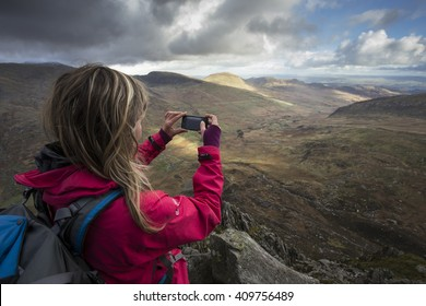 Female hill walker takes phone picture of mountain view