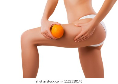 Female Hip, Beautiful Body and Orange in Hand, Overweight and Cellulite, Liposuction and Weight Loss. Model is isolated on Background with copy space.