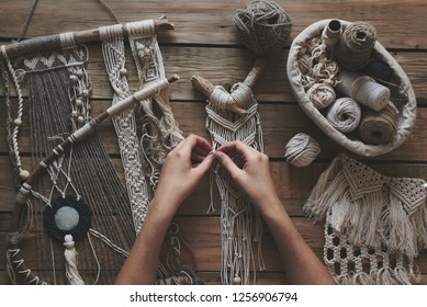 Female hobby. Hands weaving macrame on a wooden table. Do it yourself, top view.