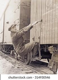 Female hobo climbing freight train