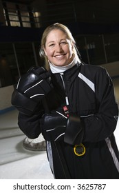 Female hockey coach in uniform standing smiling.