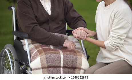Female holding aged male hand, visiting granddad in hospital, nursing home