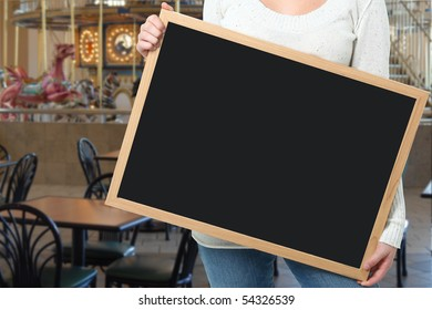 Female holding blank chalkboard in front of carousel in mall food court.
