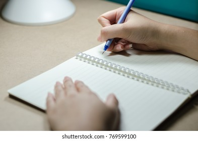 Female holding a blue pen writing on notebook on wooden table with lamp