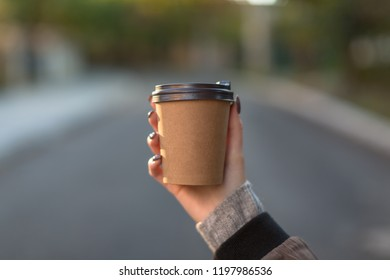 Female holding brown coffee cup