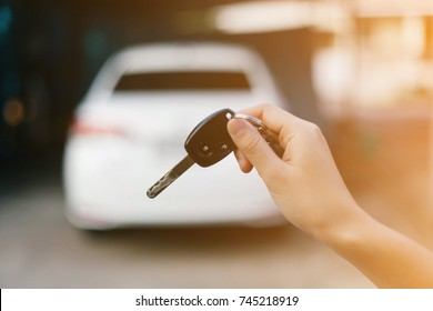 Female holding car keys with car on background.