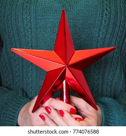 Female holding christmas red star for tops chistmas tree. Close up. Merry christmas. Christmas JOY. Decorating Cristmas tree.