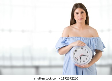Female holding a clock. Biological clock concept.
