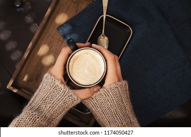 Female  holding cup of hot cappuchino coffee, Autumn fall mood, holding hands, top view , warm and cozy