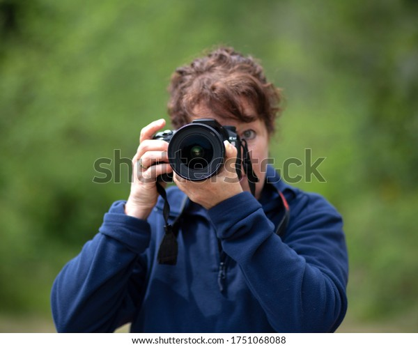 Female holding a digital camera looking directly into the image.
