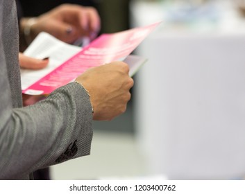 Female holding a leaflet, close up, blurred, space for text, isolated