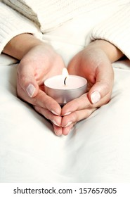 Female is holding lighted candle in hands