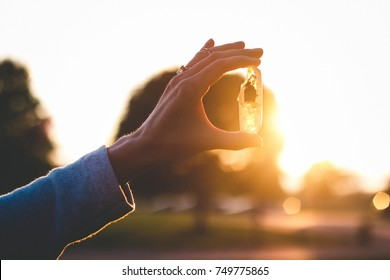 Female holding magical crystal during golden hour sunset. A photograph portraying stones for chakras, witchcraft tools, witches crystals, and/or stones.