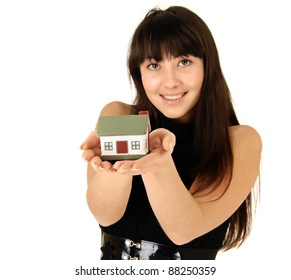 Female holding a miniature house while standing on a white background