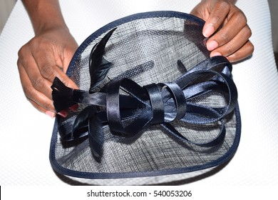 Female holding a navy blue royal ascot hat with a large bow