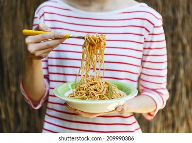 Female holding plate of spaghetti in one hand and spaghetti on fork with another