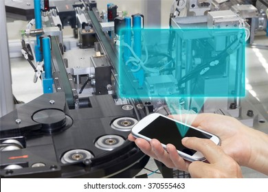 Female is holding the smart phone Blank transparent rectangle radiates from the screen smart phone. The rectangle is ready for your text. The automatic production line is in the background.