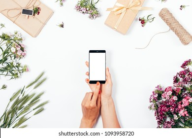 Female holding smart phone in hands among gifts and summer flowers, top view. Flat lay festive composition woman is touching screen of mobile device with her forefinger.