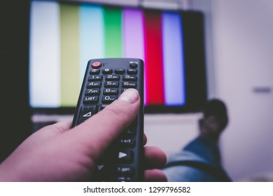 Female holding TV remote control in front of TV. Couch potatoe. Point of view shot.