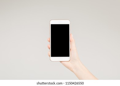 Female holding  white smartphone with blank screen in her right hand
