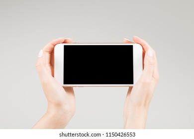 Female holding white smartphone with blank screen in two hands hands