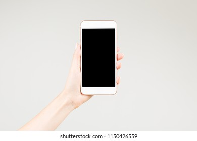 Female holding white smartphone with blank screen in her left hand