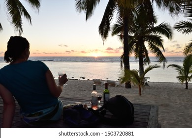 Female holiday maker having a glass of wine while watching a stunning sunset on a tropical island with palm trees and white sand beaches on Rarotonga in the Cook Islands.
