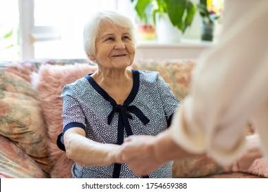 Hausfrauen, die alte Frau unterstützen, stehen zu Hause auf dem Sofa