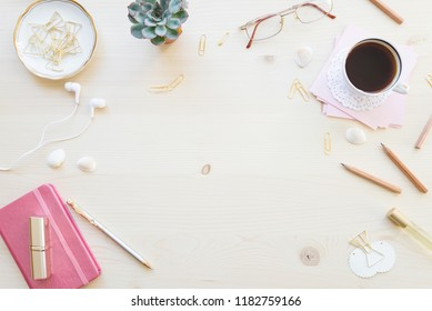 Female home office desk table in pastel tones. Workspace with notebooks, cup of coffe and decorations on light wooden background with copy-space. Flat lay, top view