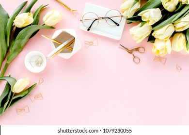 Female home office desk. Workspace with yellow tulip flowers, stationery, accessories on pink background.  Flat lay, top view.