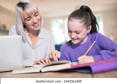 Female Home Tutor Helping Young Girl With Studies