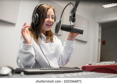 Female Host Communicating On Microphone In Radio Studio