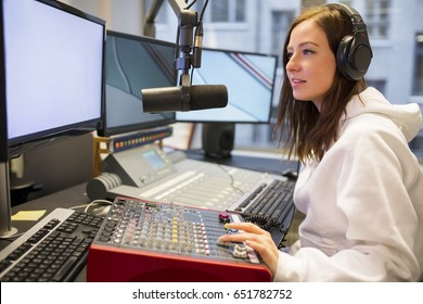 Female Host Using Control Panel At Radio Station