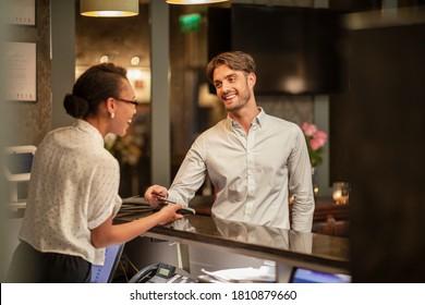 Eine Hotelrezeptionistin, die die kontaktlose Zahlung eines Kunden übernimmt, der im Hotel eincheckt, nutzt sein Smartphone, um zu bezahlen.