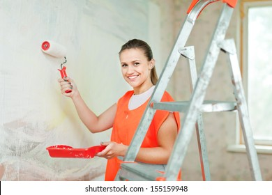 Female house painter paints wall with roller