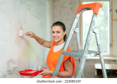 Female house painter paints wall with brush