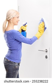 Female housekeeper cleaning a door isolated on white background