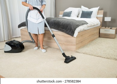 Female Housekeeper Cleaning With Vacuum Cleaner In Hotel Room