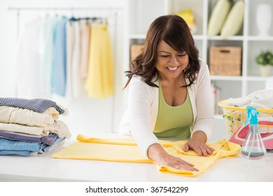Female housekeeper ironing and folding clothes in laundry room
