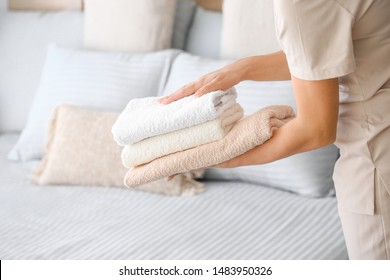 Female housekeeper putting clean towels on bed