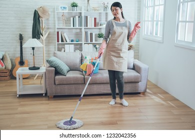 female housekeeper wearing apron and pink rubber gloves mopping the floor. young asian housewife singing clicking her finger relaxing doing housework cleaning in living room in daytime cozy apartment