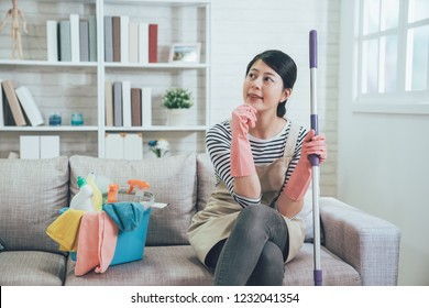 female housekeeper wearing apron sitting on couch resting with a bucket full of cleaning products after mopping the floor in the living room. young housewife holding mop thinking on couch.