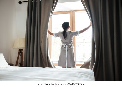 Female housekeeping chambermaid opening window curtains in the hotel room