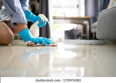 female housekeeping use alcohol spray clean surface and some stuff in the house for protect Covid-19 (coronavirus) spread and protect infected virus