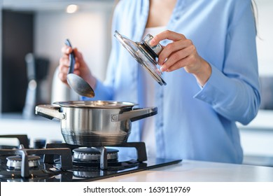 Female housewife using steel metallic saucepan for preparing dinner in the kitchen at home. Kitchenware for cooking