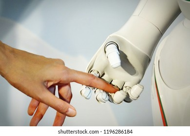 Female human hand and robot's as a symbol of connection between people and artificial intelligence technology