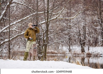 Female hunter armed with a rifle, sitting in a snowy winter forest with duck prey and grey dog.