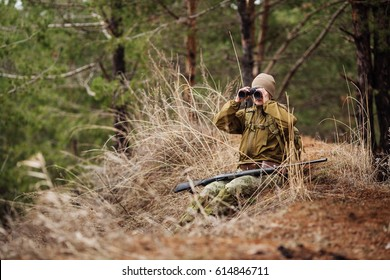female hunter with binoculars ready to hunt, holding gun and walking in forest. hunting and people concept