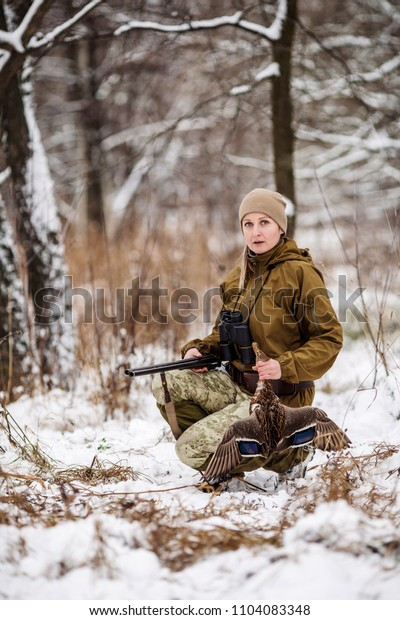 Female hunter in camouflage, armed with a rifle, sitting in a snowy winter forest with duck prey
